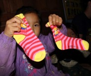 A young girl from the village delighted with her new socks that we brought as a gift to all the children
